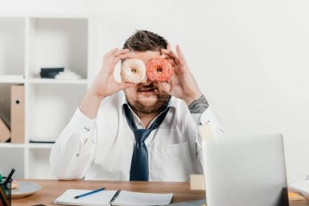 overweight businessman holding donuts in front of face in office