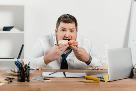 overweight businessman eating donuts at workplace with laptop