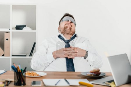 overweight businessman in sleeping mask relaxing at workplace