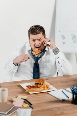 overweight businessman talking on smartphone while eating junk food at workplace