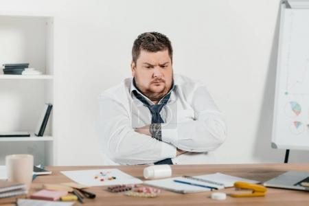 overweight businessman sitting at workplace and looking at pills