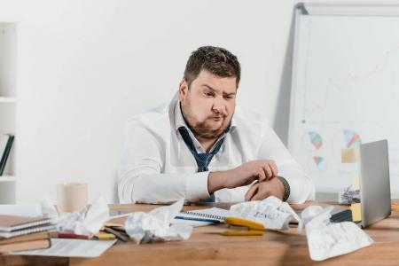 confused overweight businessman sitting at workplace with crumpled papers