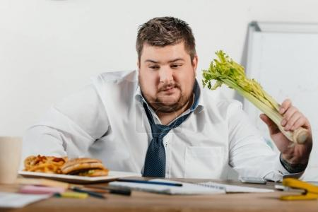 thoughtful overweight businessman choosing healthy or junk food at workplace in office