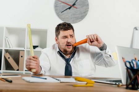overweight businessman eating fresh vegetables at workplace in office