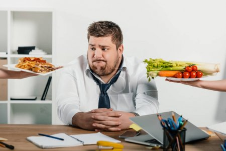 Photo for Fat businessman choosing healthy or junk food at workplace in office - Royalty Free Image