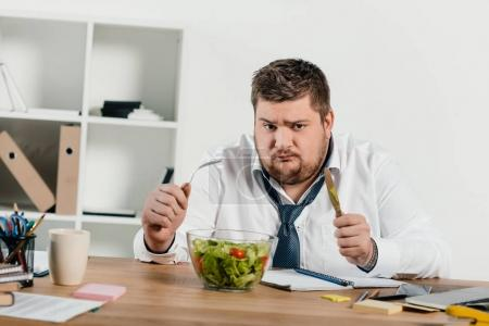 sad overweight businessman with fork and knife eating fresh salad at workplace