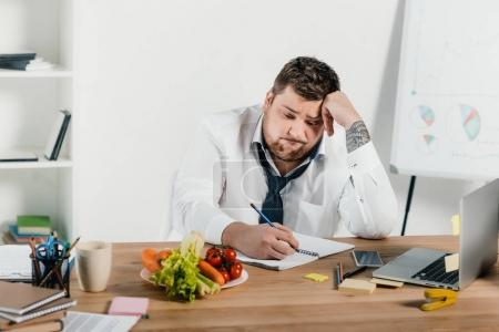 upset overweight businessman looking at vegetables while working in office