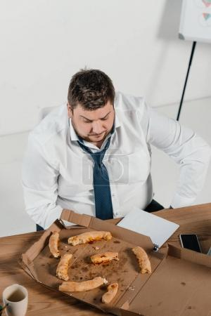 overhead view of overweight businessman eating pizza at workplace in office