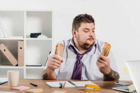 overweight businessman eating hotdogs at workplace in office
