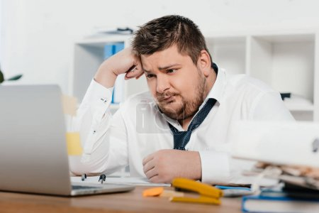 confused overweight businessman working with laptop in office