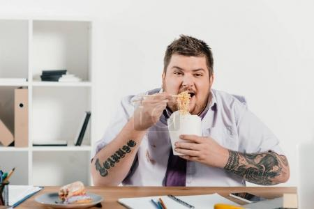 overweight tattooed businessman eating noodles at workplace in office
