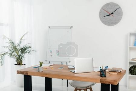 Photo for Workplace with laptop and office supplies in office with white board and clock - Royalty Free Image