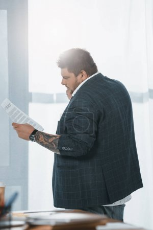 overweight businessman in suit looking at document while standing at window in office