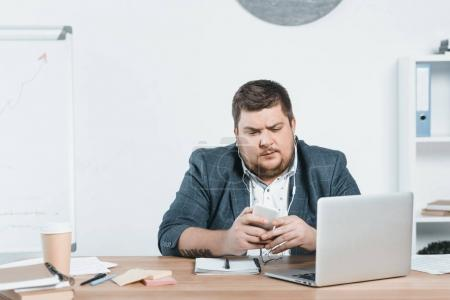overweight businessman listening music with smartphone while using laptop at workplace