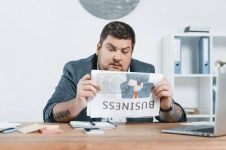 overweight businessman in suit reading business newspaper at workplace