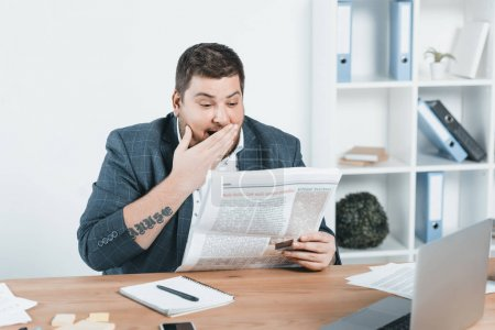 overweight businessman in suit reading newspaper at workplace