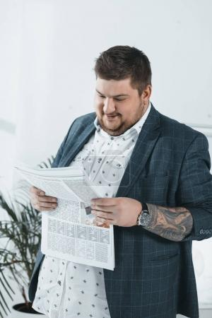fat businessman in suit reading newspaper in office