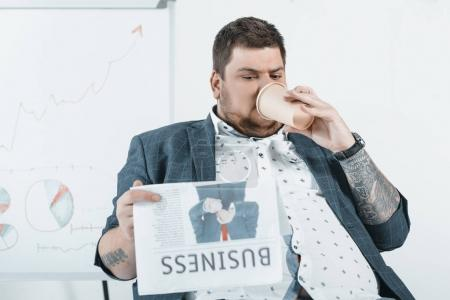 fat businessman drinking coffee and reading business newspaper in office