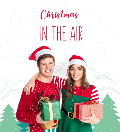 Photo for Portrait of smiling couple in santa hats with gifts in hands looking at camera isolated on white, christmas in the air lettering - Royalty Free Image