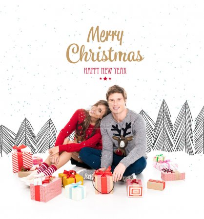 Photo for Couple in winter sweaters sitting among christmas gifts isolated on white, merry christmas and happy new year lettering - Royalty Free Image
