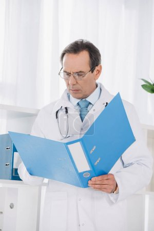 doctor holding folder and looking at documents