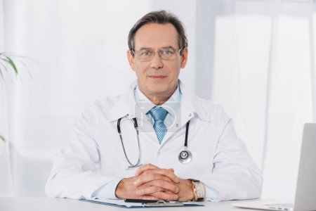 Photo for Handsome doctor in glasses sitting at working table and looking at camera - Royalty Free Image