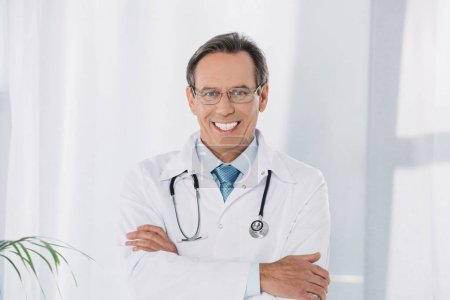 smiling doctor standing with crossed hands and looking at camera