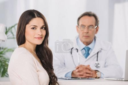 attractive female patient sitting at clinic and looking at camera