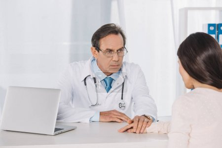 doctor and female patient holding hands at clinic