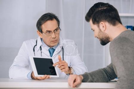 Photo pour Médecin en montrant quelque chose au patient sur tablette - image libre de droit