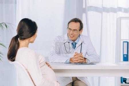 smiling doctor listening pregnant woman at clinic