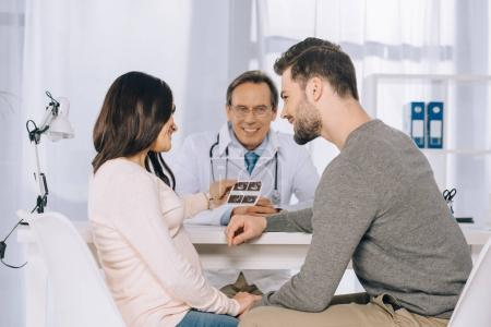 wife and husband looking at photo of ultrasound diagnostics