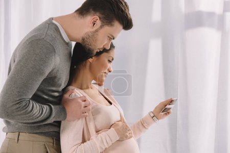 pregnant woman and husband looking at photo of ultrasound diagnostics