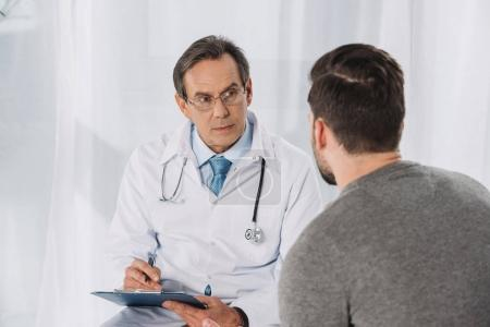 doctor holding clipboard and listening patient
