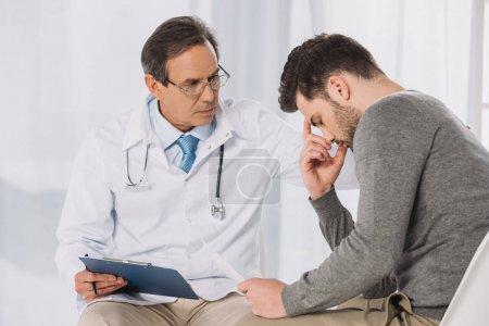 doctor putting hand on upset patient shoulder
