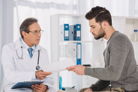 doctor giving documents to male patient