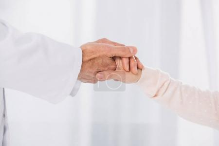 cropped image of male doctor holding female patient hand