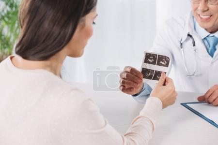 cropped image of doctor showing pregnant woman photo of ultrasound diagnostics