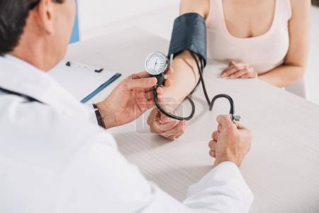 cropped image of doctor measuring patient pressure
