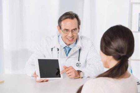 Photo pour Médecin en montrant quelque chose sur la tablette à la patiente - image libre de droit