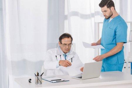 Photo pour Docteur lecture de documents et de leur donner à téter - image libre de droit