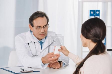 male doctor giving pills to female patient