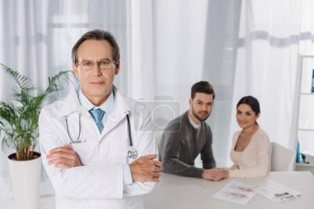 doctor standing with crossed hands on foreground