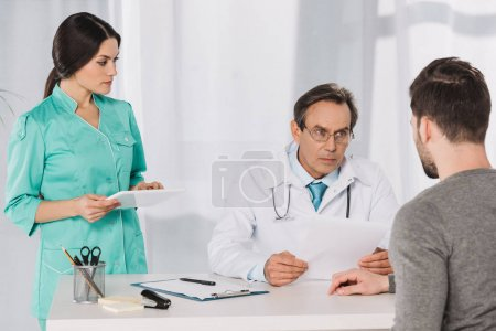 doctor talking to patient and nurse holding tablet