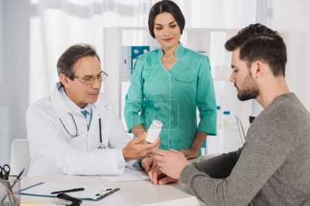 doctor giving pills to young handsome man