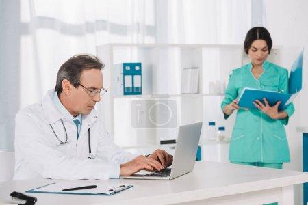 nurse searching something in folder and doctor using laptop