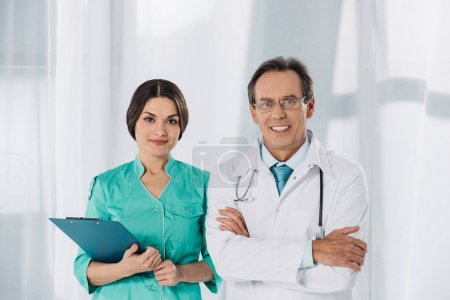 happy nurse and doctor standing and looking at camera
