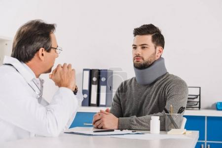 doctor talking with patient in neck brace