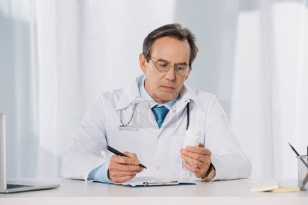 doctor holding pen and looking at pills