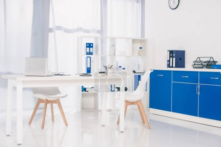 table with chairs and shelves with documents at working place in clinic
